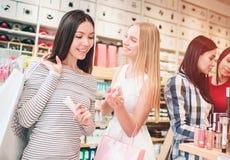 Dos muchachas agradables en el frente se están colocando y están sonriendo La muchacha asiática está mirando los cosméticos que l imágenes de archivo libres de regalías