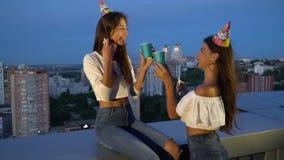 Dos muchachas alegres en casquillos festivos coloreados tintinean los vidrios con las tazas de papel que soplan en los silbidos q almacen de metraje de vídeo