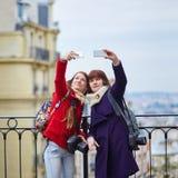 Dos muchachas alegres en París que toma el selfie usando el teléfono móvil en Montmartre Imágenes de archivo libres de regalías
