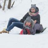Dos muchachas alegres se están sentando en la nieve Fotos de archivo libres de regalías