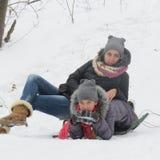Dos muchachas alegres se están sentando en la nieve Fotografía de archivo libre de regalías