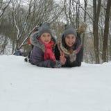 Dos muchachas alegres se están sentando en la nieve Imágenes de archivo libres de regalías