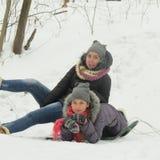 Dos muchachas alegres se están sentando en la nieve Imagen de archivo libre de regalías