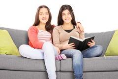 Dos muchachas asentadas en el sofá que abraza y que mira la cámara Imagen de archivo libre de regalías