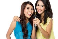 Dos muchachas asiáticas en camiseta rayada que cantan junto Fotos de archivo