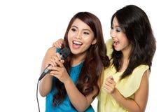 Dos muchachas asiáticas en camiseta rayada que cantan junto Imagen de archivo