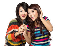 Dos muchachas asiáticas en camiseta rayada que cantan junto Fotografía de archivo