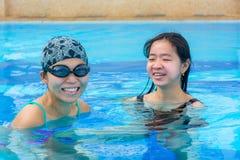 Dos muchachas asiáticas se están divirtiendo en la piscina Fotografía de archivo libre de regalías