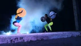 Dos muchachas atléticas, atletas, aumentan el barbell, hacen sentar-UPS con el barbell En la noche, teniendo en cuenta los reflec metrajes