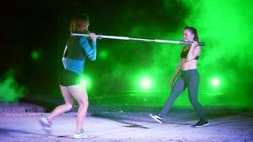Dos muchachas atléticas en los pares que hacen diversa fuerza ejercitan con un barbell, estocadas, posiciones en cuclillas, en la almacen de video