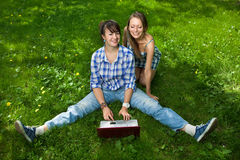Dos muchachas atractivas con una computadora portátil en el parque Imagen de archivo