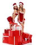 Dos muchachas atractivas de la Navidad que presentan con una pila de presentes imagen de archivo libre de regalías