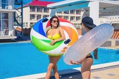 Dos muchachas atractivas del inconformista que caminan con la natación circundan cerca de piscina Imagen de archivo libre de regalías