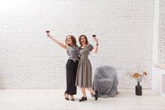 Dos muchachas atractivas, divirtiéndose y bebiendo el vino rojo en partido De moda vestida con el pelo ondulado hermoso En desván imágenes de archivo libres de regalías
