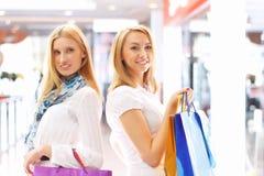 Dos muchachas atractivas hacia fuera que hacen compras Foto de archivo libre de regalías