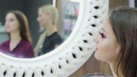 Dos muchachas atractivas jovenes, una morenita y un rubio, actitud para la cámara en un salón de belleza con una reflexión en el  metrajes