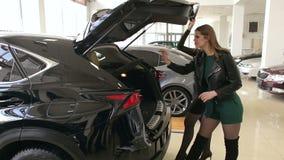 Dos muchachas atractivas lujosas eligen un nuevo coche en la sala de exposición Compra de un nuevo coche metrajes