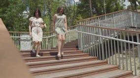 Dos muchachas atractivas que llevan los vestidos del verano que corren abajo de las escaleras en el parque de la ciudad Novias de almacen de video