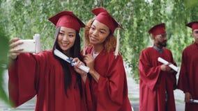 Dos muchachas atractivas que los estudiantes compañeros están tomando el selfie el día de graduación que sostiene los diplomas, m metrajes