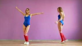 Dos muchachas bailan danzas modernas Mujeres en trajes de baño y calentadores de la pierna almacen de metraje de vídeo