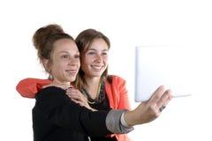 Dos muchachas bastante adolescentes que toman selfies con su tableta digital Imagen de archivo