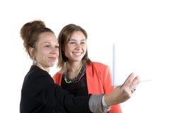 Dos muchachas bastante adolescentes que toman selfies con su tableta digital Foto de archivo libre de regalías