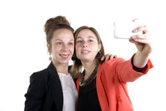 Dos muchachas bastante adolescentes que toman selfies con su teléfono elegante Foto de archivo libre de regalías