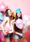 Dos muchachas bastante emocionales celebran los globos y la presentación contra el perno Fotografía de archivo libre de regalías