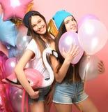 Dos muchachas bastante emocionales celebran los globos y la presentación contra el perno Foto de archivo