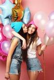 Dos muchachas bastante emocionales celebran los globos y la presentación contra el perno Fotos de archivo libres de regalías