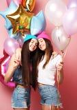 Dos muchachas bastante emocionales celebran los globos y la presentación contra el perno Imágenes de archivo libres de regalías