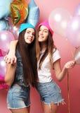 Dos muchachas bastante emocionales celebran los globos y la presentación contra la pared rosada Imagen de archivo