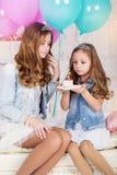 Dos muchachas bonitas con la torta y los globos de cumpleaños Foto de archivo