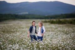 Dos muchachas bonitas del niño están caminando en el campo de la manzanilla Fotos de archivo