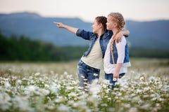 Dos muchachas bonitas del niño están caminando en el campo de la manzanilla Fotos de archivo libres de regalías