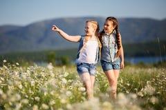 Dos muchachas bonitas del niño están caminando en el campo de la manzanilla Imagenes de archivo