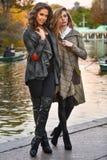 Dos muchachas bonitas en las capas elegantes que presentan en otoño parquean Fotos de archivo libres de regalías