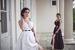 Dos muchachas bonitas en vestidos largos blancos y negros Imagen de archivo