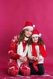 Dos muchachas bonitas están llevando la ropa del invierno en estudio Imagen de archivo libre de regalías