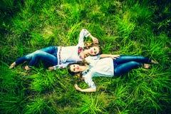 Dos muchachas bonitas felices que mienten en la hierba verde Imagenes de archivo
