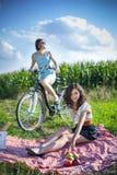 Dos muchachas bonitas hacen una comida campestre en campo Imágenes de archivo libres de regalías