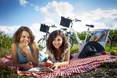 Dos muchachas bonitas hacen una comida campestre, leyendo un libro Foto de archivo