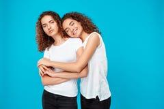 Dos muchachas bonitas jovenes hermanan el abarcamiento, sonriendo sobre fondo azul Imagen de archivo