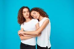 Dos muchachas bonitas jovenes hermanan el abarcamiento, sonriendo sobre fondo azul Fotos de archivo libres de regalías