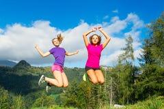 Dos muchachas bonitas jovenes que saltan en la hierba en un scener de la montaña Foto de archivo libre de regalías