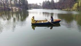 Dos muchachas bonitas jovenes que se sientan en el bote peque?o en el medio del lago o del r?o reflexivo hermoso Forma de vida ac almacen de video
