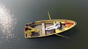 Dos muchachas bonitas jovenes que se sientan en el bote peque?o en el medio del lago o del r?o reflexivo hermoso Forma de vida ac metrajes