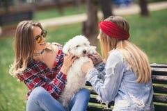 Dos muchachas bonitas que juegan con el perrito lindo Fotos de archivo libres de regalías