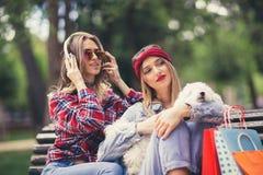 Dos muchachas bonitas que juegan con el perrito lindo Foto de archivo