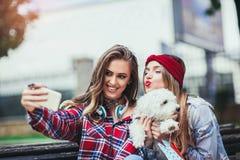 Dos muchachas bonitas que juegan con el perrito lindo en el parque Fotografía de archivo